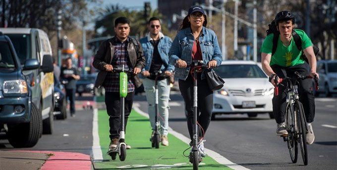 Group of people riding electric scooters in designated bike lane