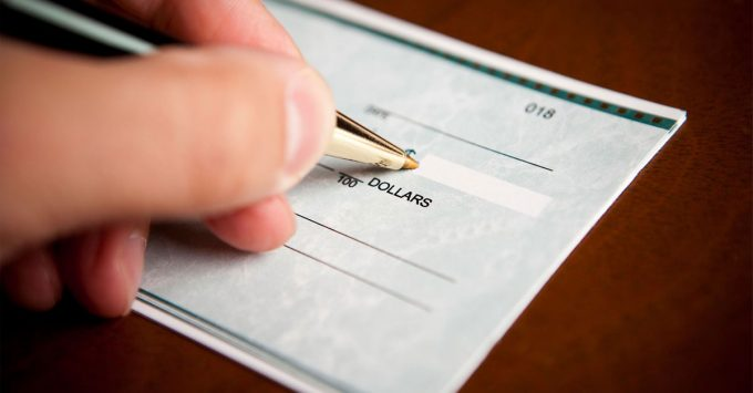 A closeup of a hand signing a blank check
