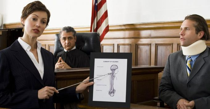 Female personal injury lawyer in court presenting a spinal injury visual aid